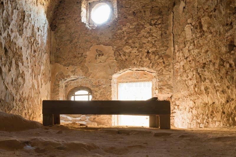 Nafplio, Grecia, el 28 de diciembre de 2015 Cama de madera vieja dentro de la vieja celda de prisión en el castillo de Palamidi e foto de archivo