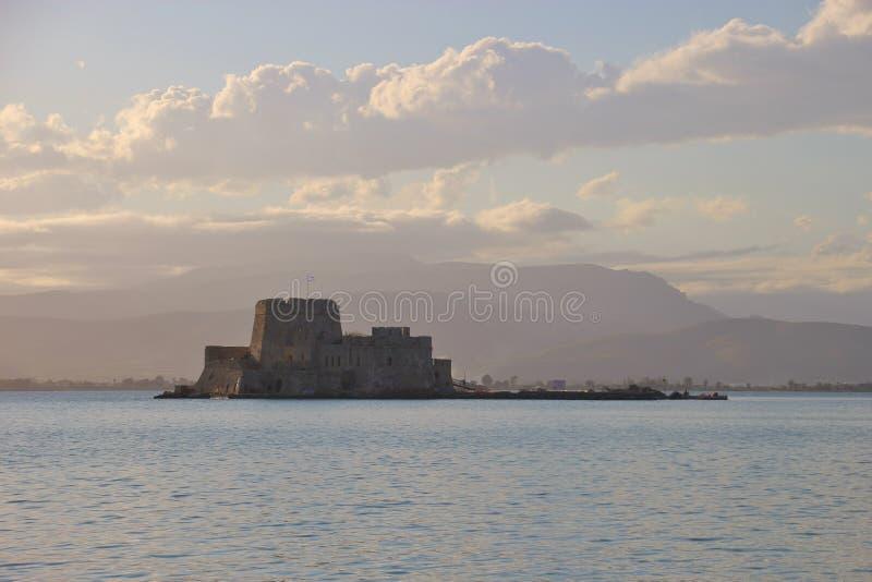Nafplio, Peloponnese, Greece. Bourtzi castle and mountain landscape in pastel colors. Shortly before sunset in the bay of Nafplio, Peloponnese, Greece. Bourtzi royalty free stock image