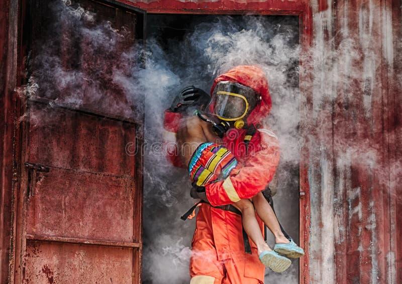 Nagłego wypadku ogienia ratuneku szkolenie, strażacy save chłopiec od bu fotografia stock