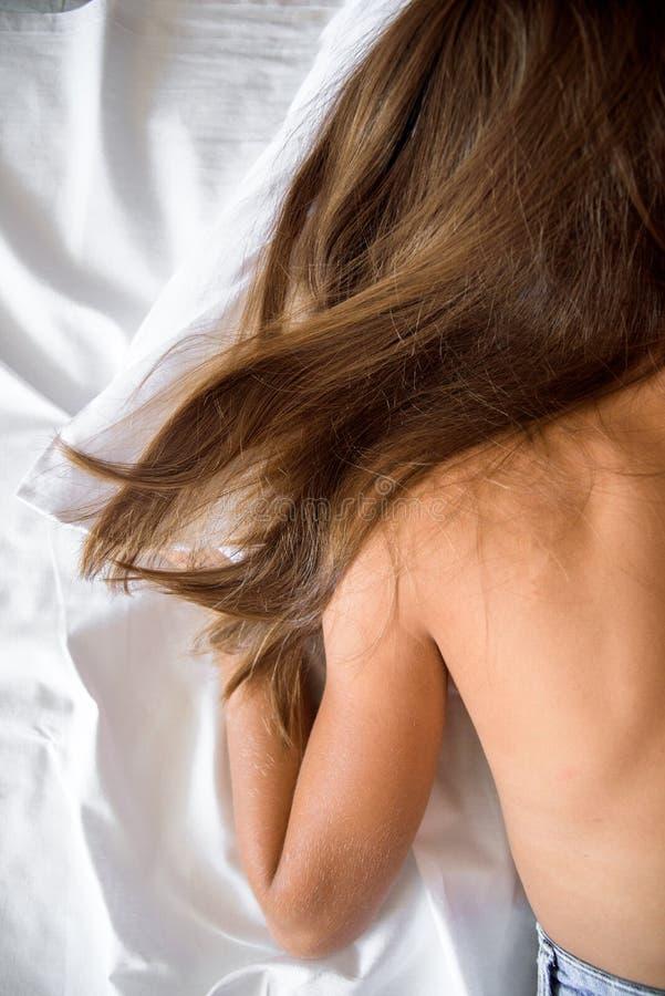 Naga dziewczyna na łóżkowej brunetce z długie włosy sen z nagim z powrotem na białym łóżku Biała koc i pościel obrazy royalty free