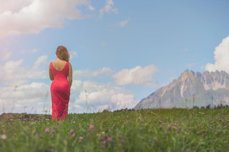 Naga kobieta w czerwonej sukni w polu przy zmierzchem obrazy royalty free