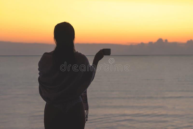 Naga piękna kobieta z mokrym włosy zawijającym w koc z filiżanka kawy pozycją na szklanym balkonowym wczesnym poranku przy sunris zdjęcia stock