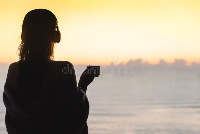 Naga piękna kobieta z mokrym włosy zawijającym w koc z filiżanka kawy pozycją na szklanym balkonowym wczesnym poranku przy sunris obrazy stock