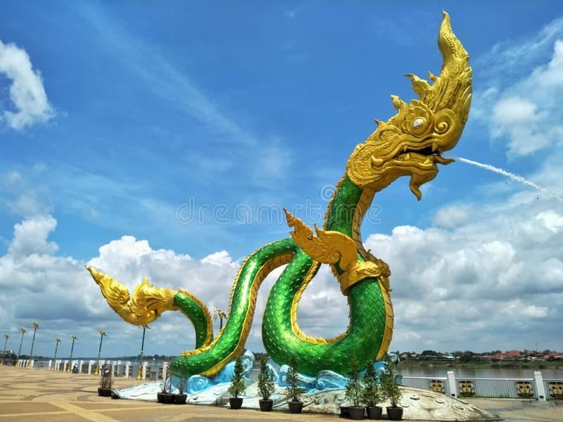 Naga statues are landmark and public area of Nong Khai province of Thailand. Art, serpent, green, gold, sky, cloud, blue, white, background, nature, religion royalty free stock photos