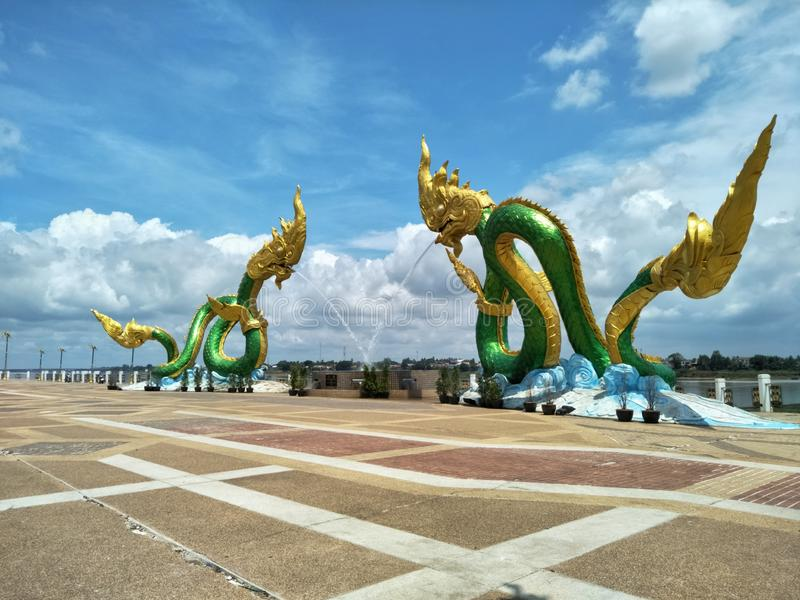 Naga statues are landmark and public area of Nong Khai province of Thailand. Serpent, sky, cloud, white, blue, floor, patio, asia, cloudy, park, mekong, river stock images