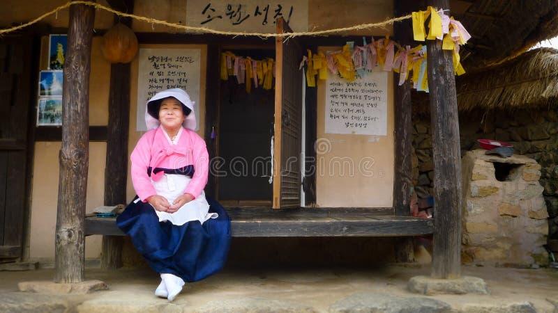 Nagan/Korea-29 sul 05 2018: A mulher no vestido tradicional que senta-se dentro da vila popular de Naganeupseong imagem de stock