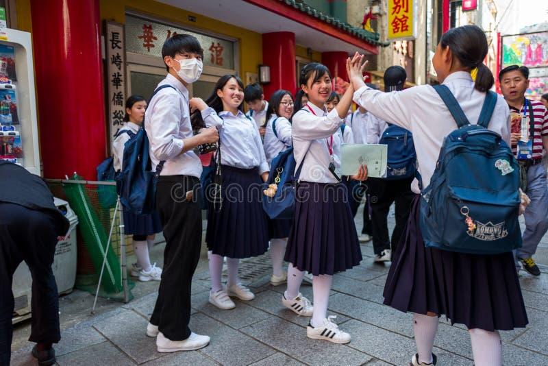 Nagasaki, Japón - 18 de mayo: Los estudiantes no identificados en uniformes escolares se divierten en la ciudad de China el 18 de fotografía de archivo libre de regalías