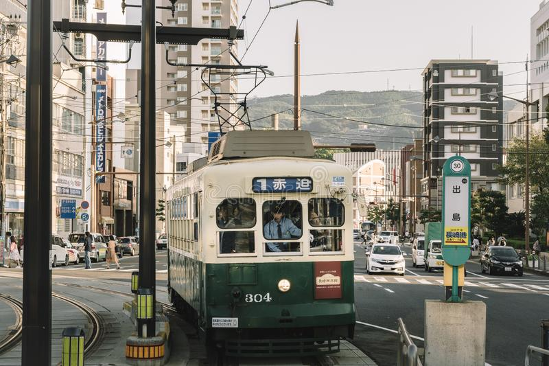 Nagasaki, Kyushu, Japan, East Asia - Oct 7 2017: An old crowded tram coming into the platform. Public transportation in downtown. Urban landscape. City walking stock images