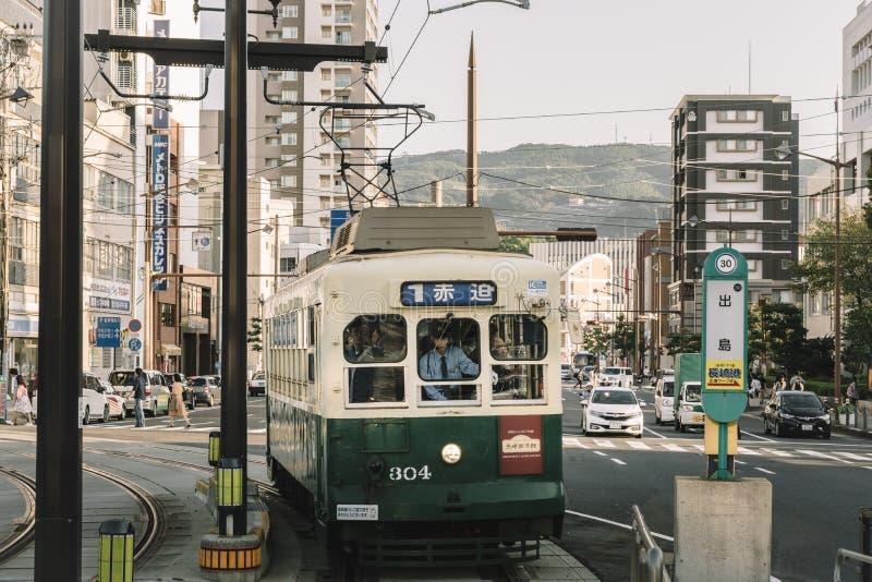 Nagasaki Kyushu, Japan, East Asia - Oktober 7 2017: En gammal fullsatt spårvagn som kommer in i plattformen arkivbilder