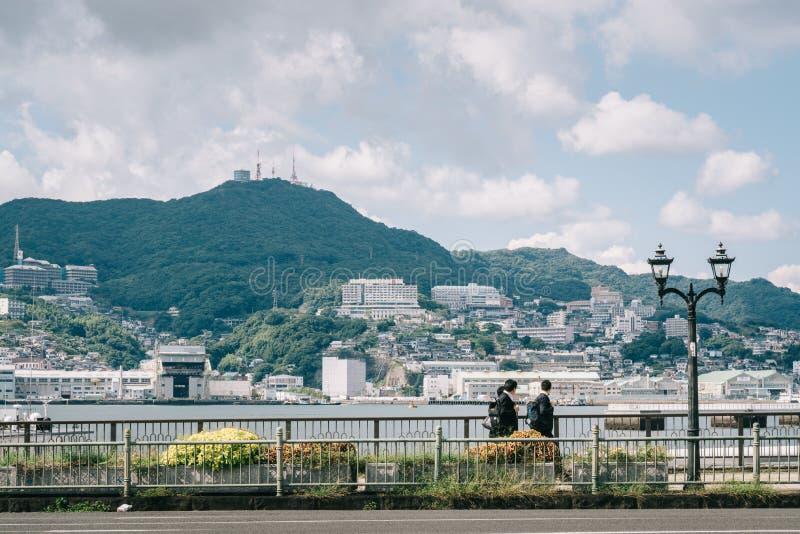Nagasaki Kyushu, Japan, East Asia - studenter som hem går efter skola i en bakgrund av det härliga landskapet med havet och berge arkivbild