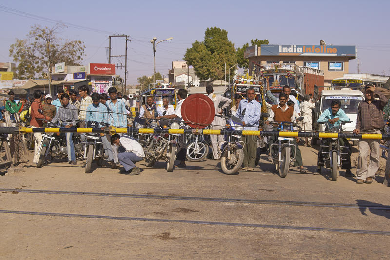 Nagaur Livestock Fair, India. Crowd of vehicles fill the road waiting for the barriers to rise at a level crossing in Nagaur, India royalty free stock images