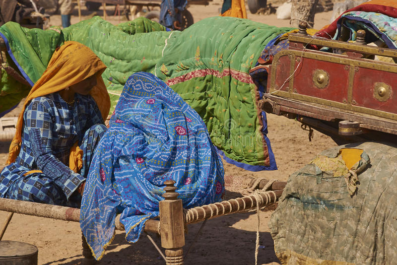 Nagaur Livestock Fair, India. Women in brightly coloured clothing sitting on a bed, known as a charpoy, at the annual livestock fair in Nagaur, India royalty free stock photography