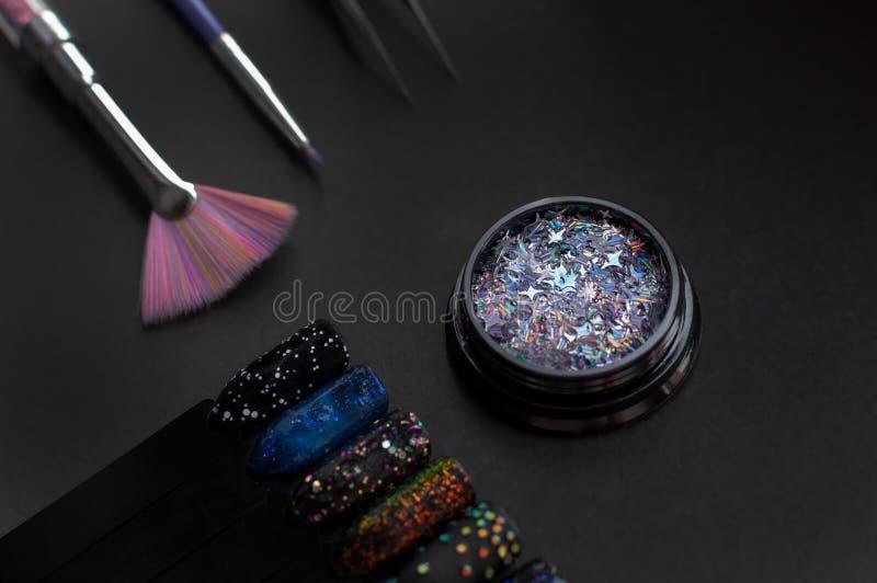 Nagelkunstproben und -zusätze auf schwarzem Hintergrund Schwarze Nagelspitzen mit Funkeln und sternenklarer Nagelkunst des nächtl stockfoto