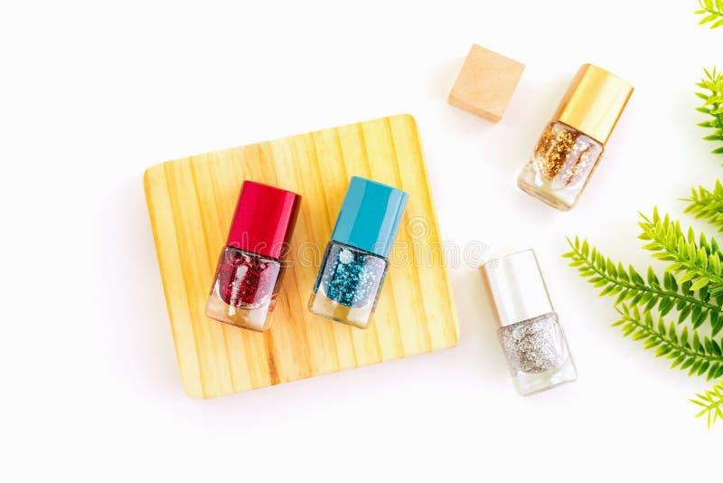 Nagellak van mooie kleurrijk op houten platform en witte achtergrond stock foto's