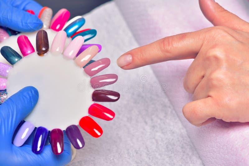 Nagelpflege und Maniküre Nahaufnahme der schönen Frau übergibt Applyi lizenzfreie stockbilder