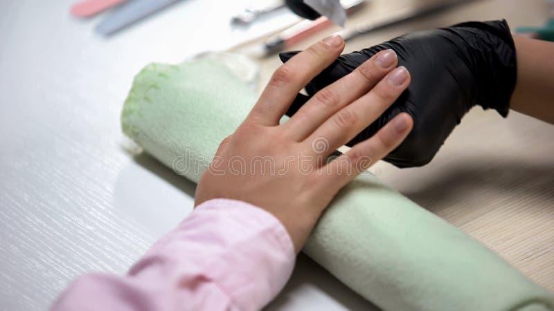Nagelt de manicure hoofd oppoetsende cliënten alvorens lak, schoonheidsprocedure te zetten stock afbeelding