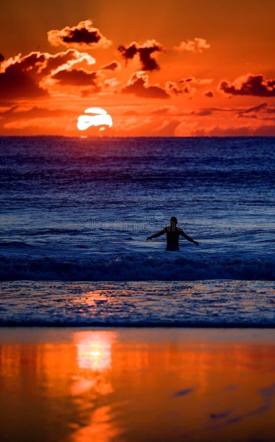 Nageur dans l'océan au coucher du soleil photo stock