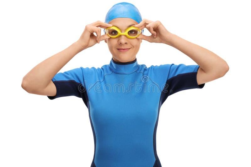 Nageur féminin ajustant ses lunettes de natation photo stock