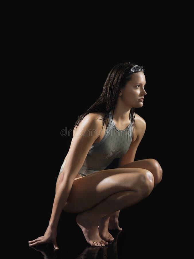 Nageur féminin sérieux Crouching images stock