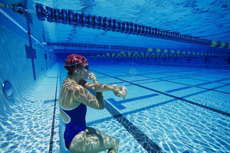 Nageur féminin se reposant sous l'eau photo stock