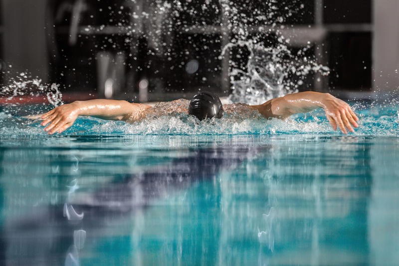 Nageur masculin nageant la course de papillon photographie stock