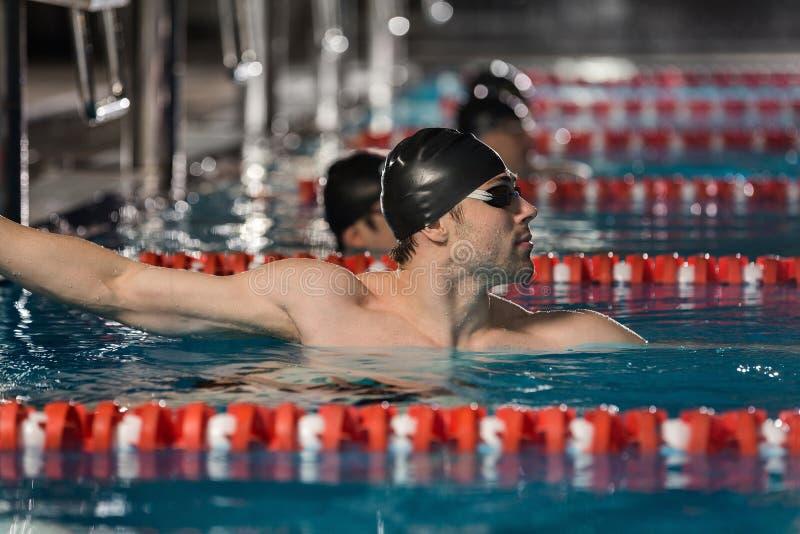 Nageur masculin tenant le bord d'une piscine photo stock