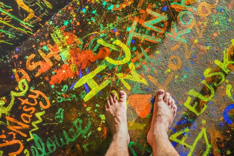 Nagi ludzki bosy na fluo neonowej malującej podłoga przy plaży przyjęciem zdjęcie royalty free
