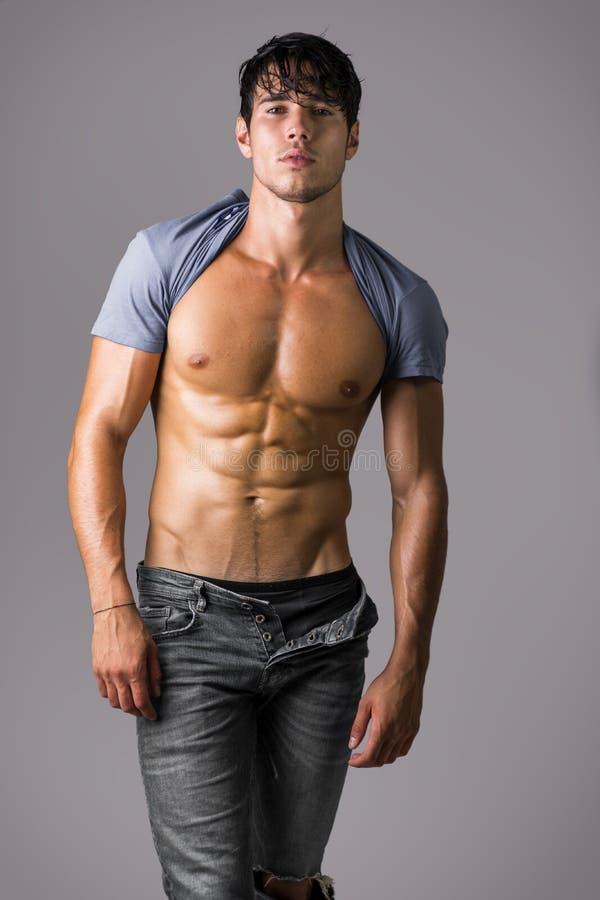 Nagi mięśniowy mężczyzna jest ubranym tylko cajgi obraz stock