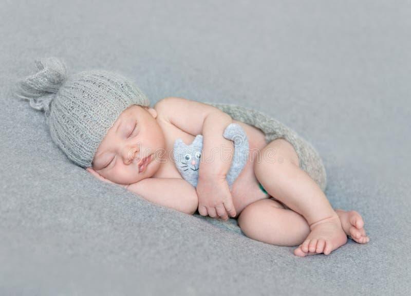 Nagi nowonarodzony dziecko w szarym kapeluszu z zabawką fotografia stock