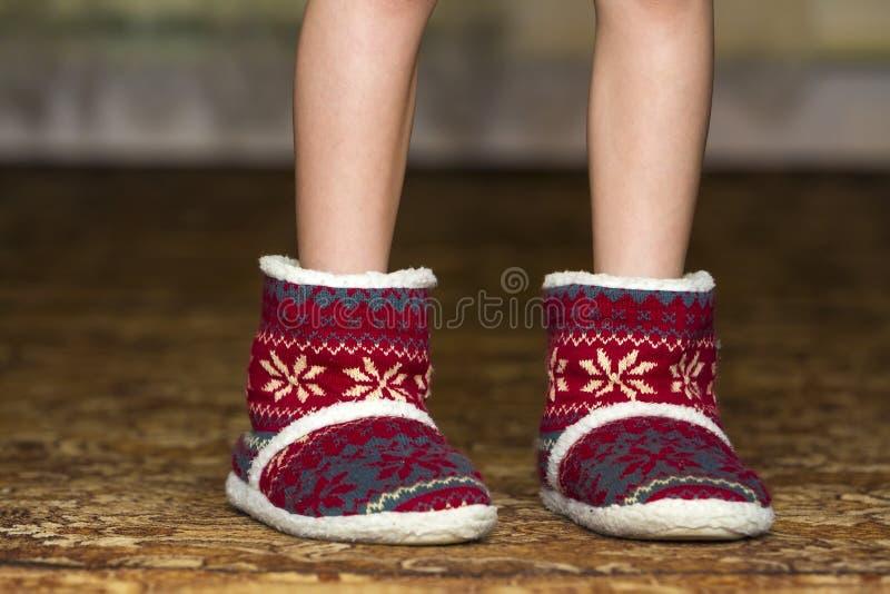 Nagie dziecko nogi, cieki w czerwonych zim bożych narodzeń butach z orna i obraz stock