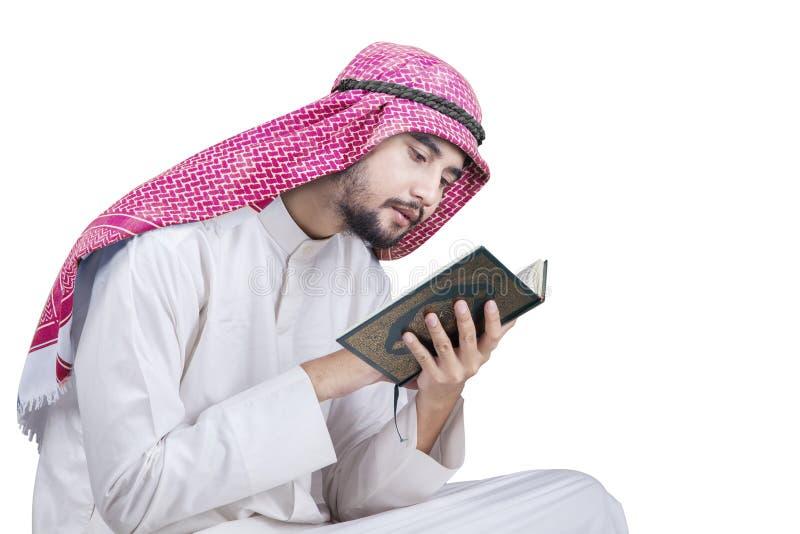 Nahöstlicher Mann liest Quran im Studio lizenzfreie stockbilder