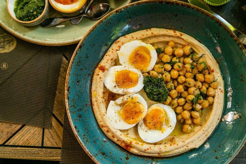 Nahöstliches Zauntrittfrühstück - hummus mit Eiern, Pittabroten und Bädern lizenzfreie stockbilder