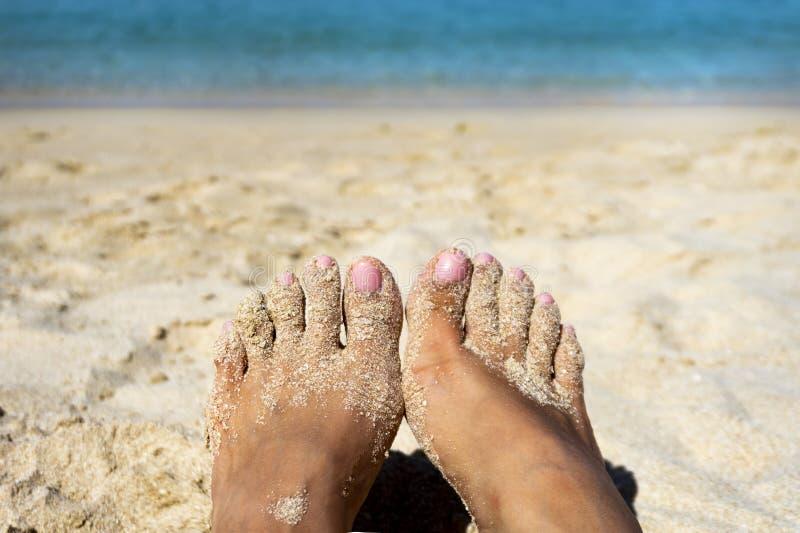 Nah bräunen Sie oben sich barfuß mit einem kleinen Sand auf Strandhintergrund stockfoto