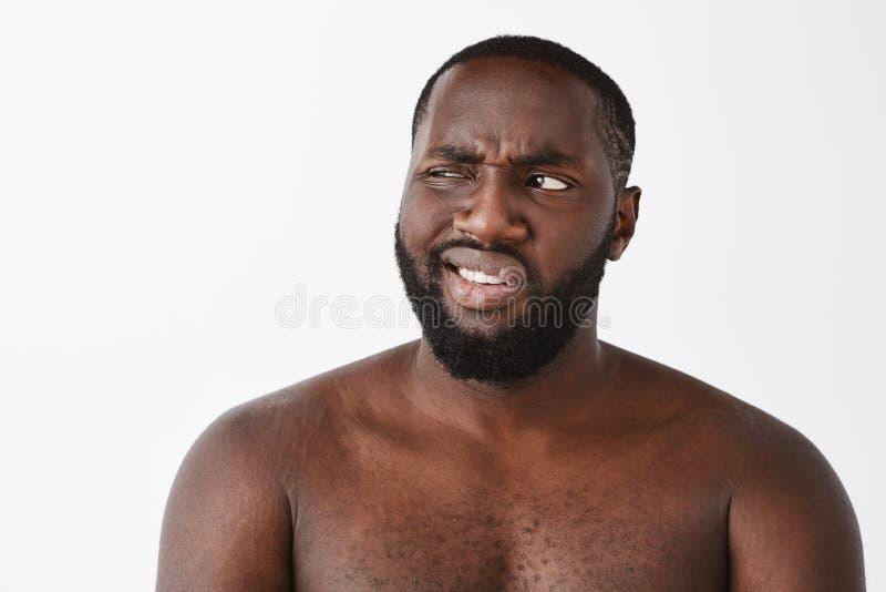 Nah mala idea Retrato del varón desnudo de piel morena maduro apuesto descontentado con la barba, bizqueando mientras que mira fi imágenes de archivo libres de regalías