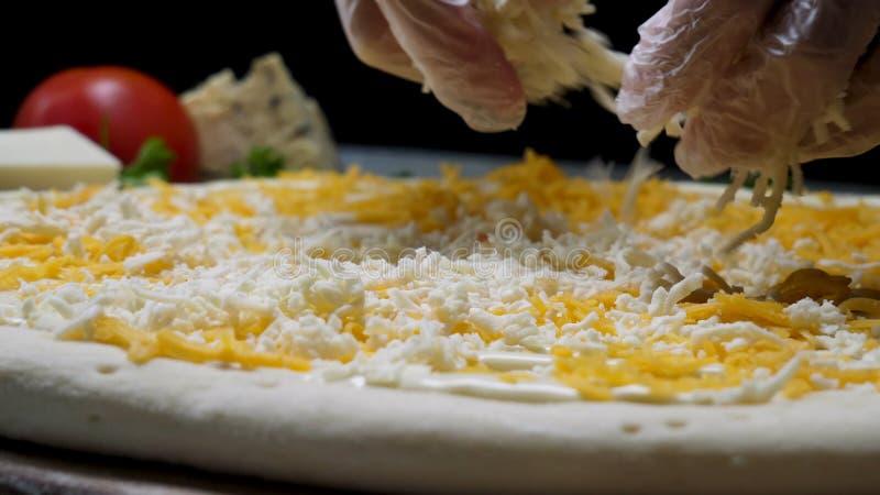 Nah oben für die Hände des Kochs, wenn die Handschuhe gekocht werden, die Käse auf die Pizza vier Käse setzen Feld Chef, der die  stockfotos