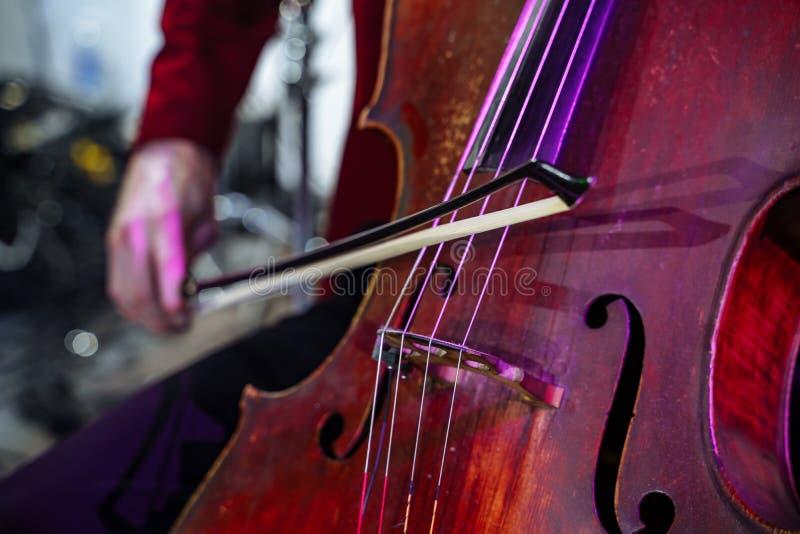 Nah - oben vom Musikinstrumentcello Die Hände der Männer, die das Instrument spielen lizenzfreies stockfoto