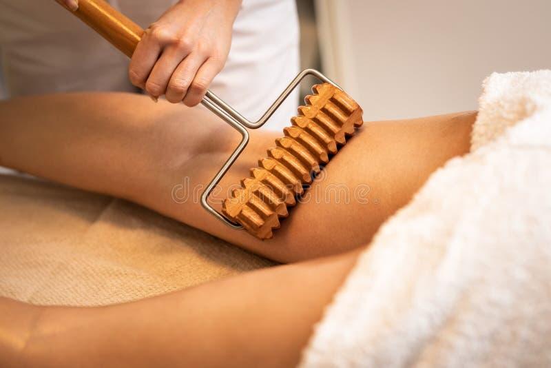 Nah oben von anticellulite Massage mit maderotherapy hölzernem Nudelholz lizenzfreie stockfotos