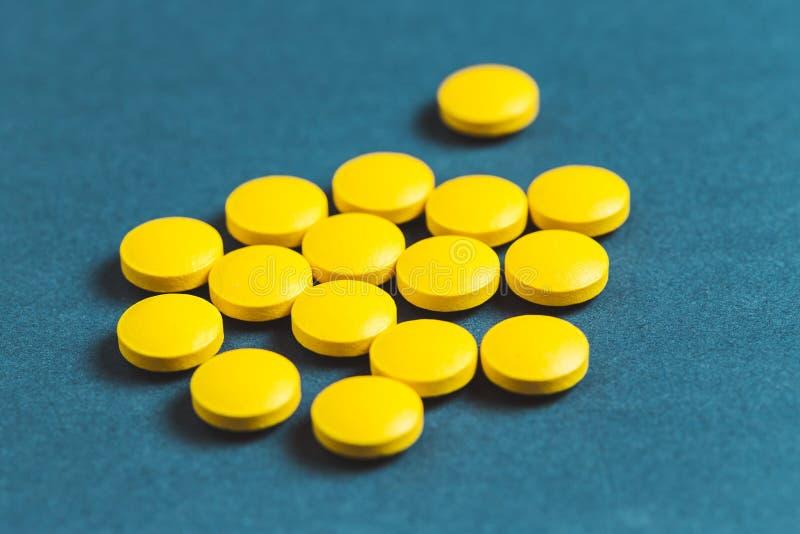 nah oben von den gelben Pillen auf einem blauen Hintergrund lizenzfreie stockfotografie