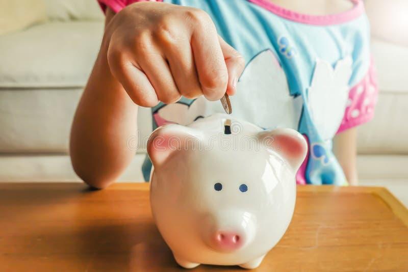 Nah oben von der Hand des Mädchens, die Münze zum Sparschwein setzt lizenzfreies stockfoto