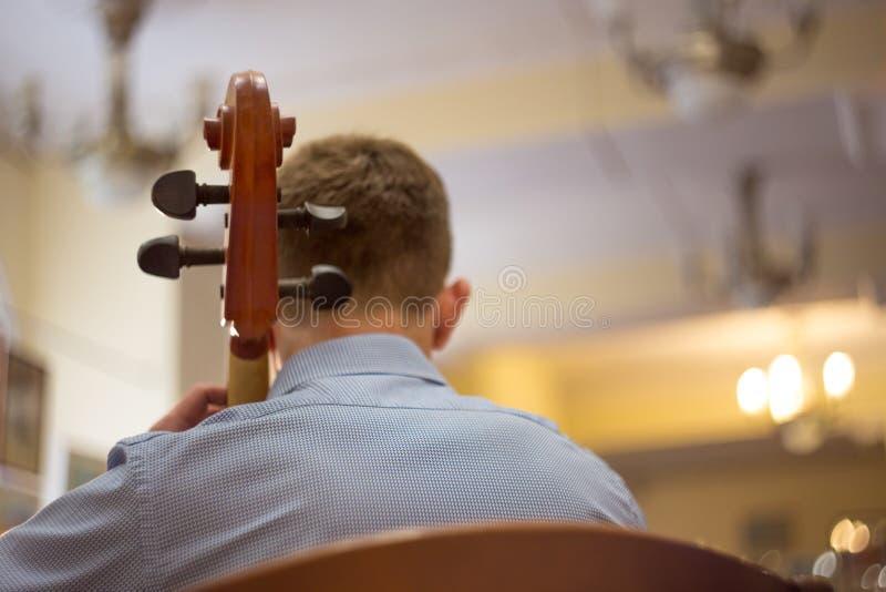 nah oben von einem Mann, der das Cello, ein wirkliches Konzert, hintere Ansicht spielt stockfotografie