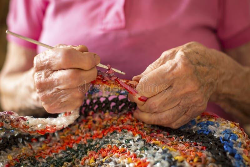 Nahaufnahme übergibt astringierende Häkelarbeit einer älteren Frau liebhaberei lizenzfreie stockfotografie