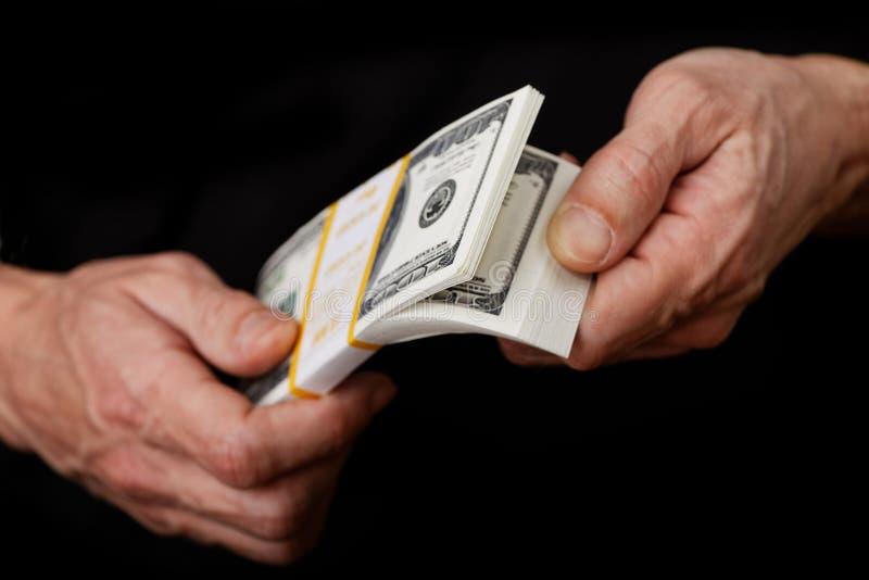 Nahaufnahme übergibt das Nachzählen von Banknoten in einem Bündel Dollar lizenzfreie stockfotografie