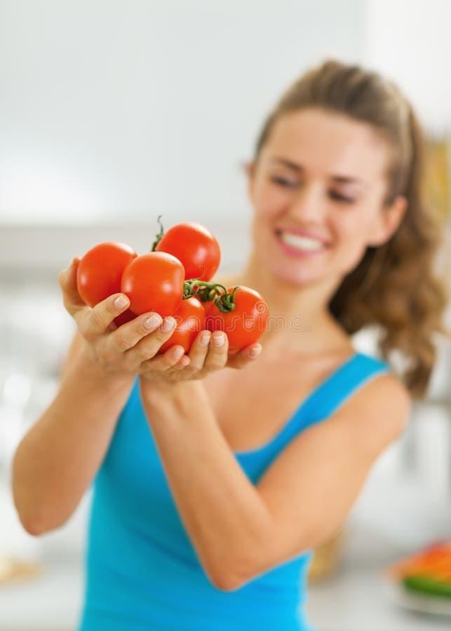 Nahaufnahme auf Bündel der Tomate in der Hand der jungen Frau lizenzfreie stockbilder