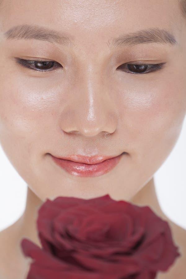 Nahaufnahme auf dem Gesicht der lächelnden Schönheit unten betrachtend einer roten Rose, Atelieraufnahme stockbild