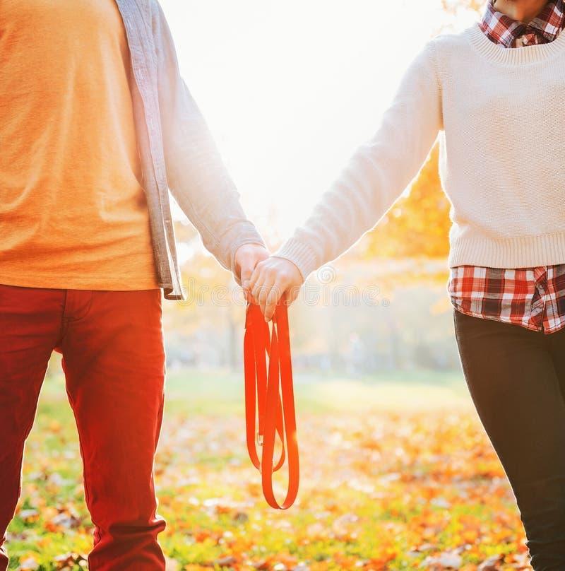 Nahaufnahme auf den Paaren, die Leine im Herbstpark zusammenhalten stockfotografie