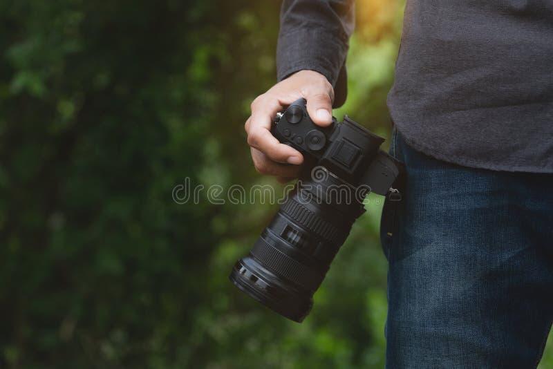 Nahaufnahme auf der Fotografhand, die Kamera hält lizenzfreie stockbilder