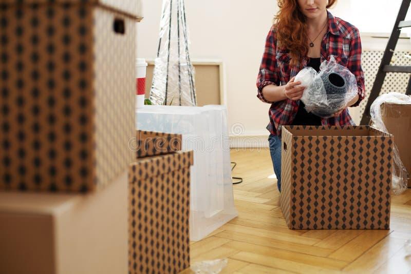 Nahaufnahme auf der Frau, die den Vase mit Folie beim Verpacken in Kästen schützt lizenzfreie stockfotos