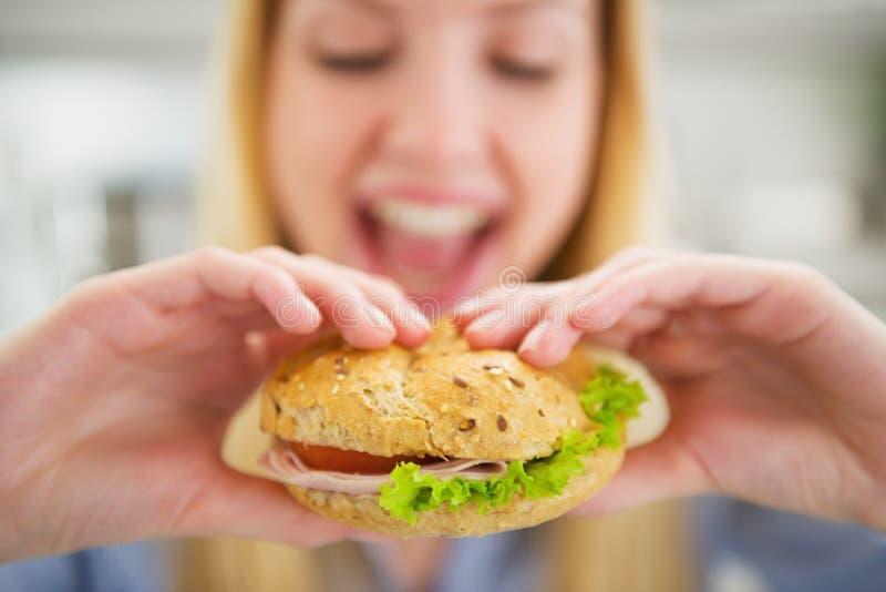 Nahaufnahme auf der glücklichen jungen Frau, die Burger isst lizenzfreies stockfoto