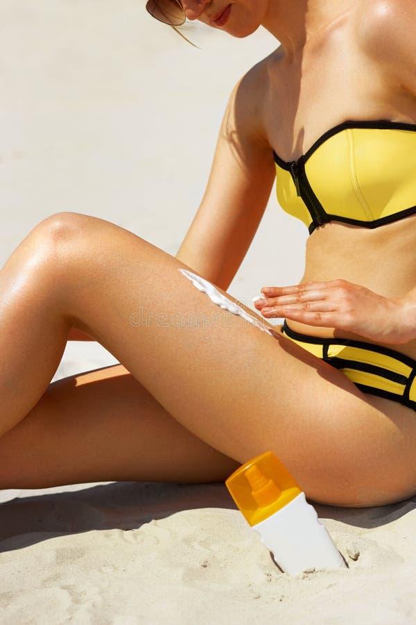 Nahaufnahme auf der weiblichen Hand, die Lichtschutzcreme auf Bein anwendet Skincare Sonnenschutzsonnencreme, auf ihren glatten g stockfoto