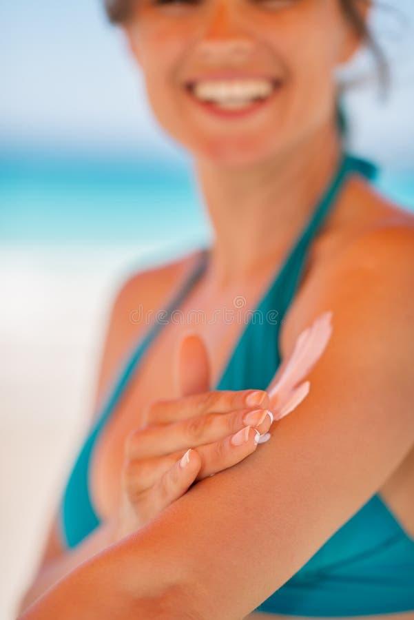 Nahaufnahme auf der weiblichen Hand, die Sonneblockcreme anwendet lizenzfreie stockfotografie